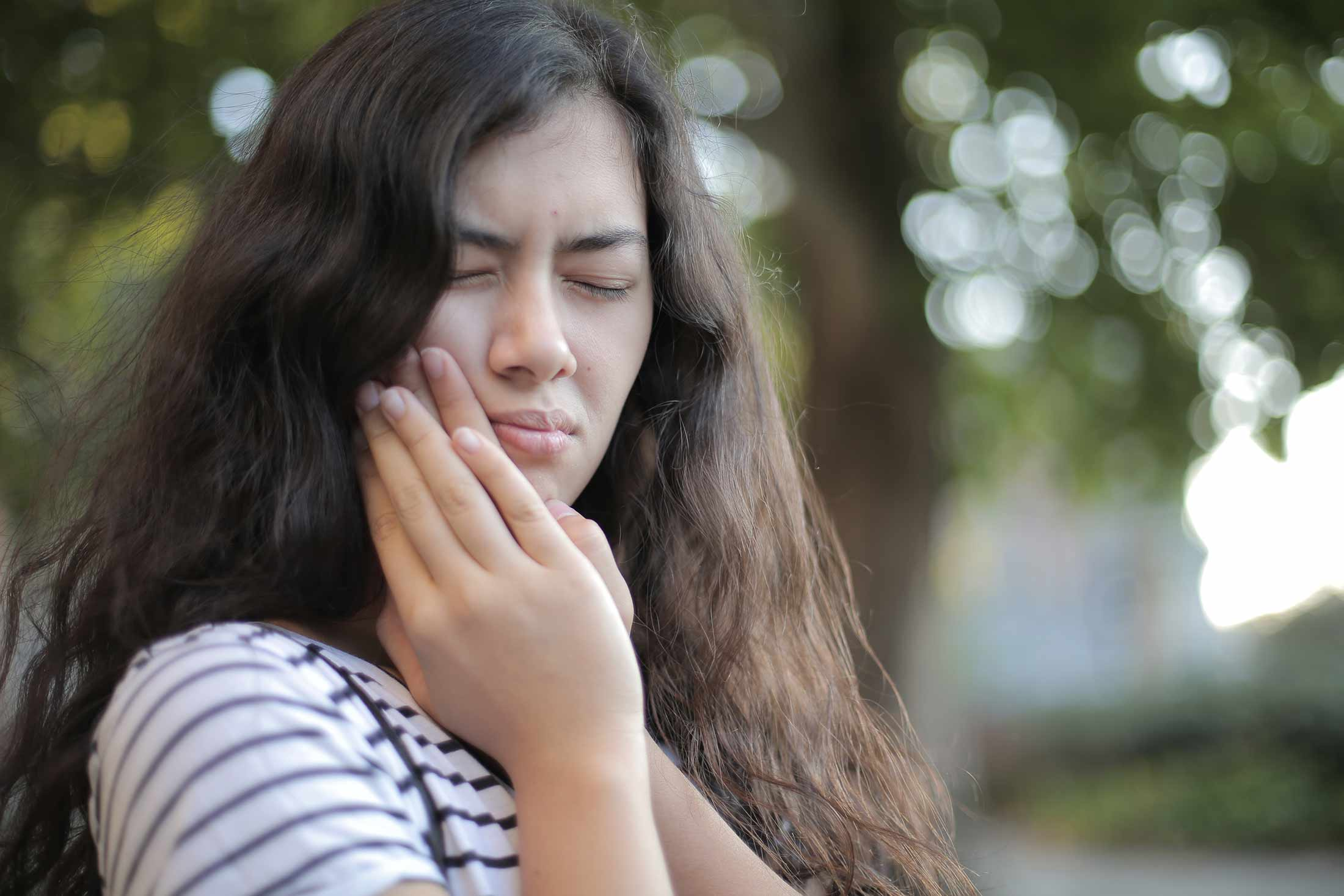 a young woman holds her jaw and looks to be in pain