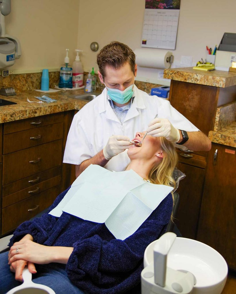 Dr. Dustin Ebner cleans the teeth of a patient at Ebner Family Dentistry
