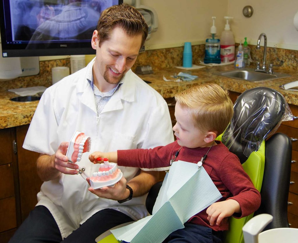 Dr. Dustin Ebner teaches tooth brushing to a young patient at Ebner Family Dentistry